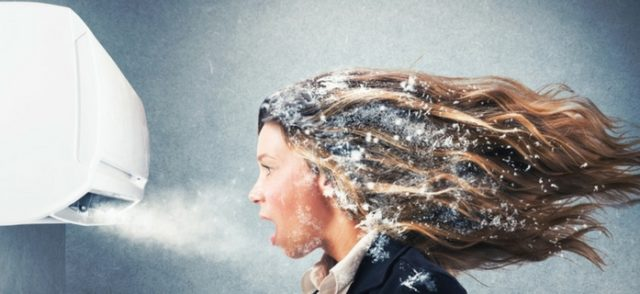 Woman with snow blown into her hair by an ac unit wondering what she should do with her ac during the winter